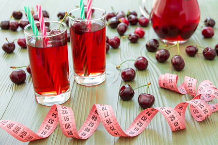 a jar stand: Left 2 glasses of juice with straws, scattered cherries, jar of cherry juice, in front centimeter on light green background. Cherries, cherry juice and centimeter. Horizontal. Stock Photo