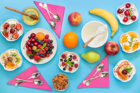 differently: 6 bowls of yogurt dressed with different ingredients fruit, berries, nuts, honey, and 6 spoons, napkins on light blue background. Six differently dressed yogurts and ingredients. Horizontal. Top view. Stock Photo