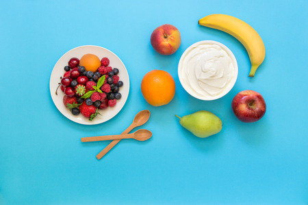 dairy product: Greek yogurt around orange, banana, pear, peach, apple, plate with strawberries, raspberries, blueberries and two wooden spoons on light blue background. Horizontal. Top view.