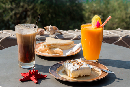 gastro: Coffee, orange juice, cheese ham toast, ekmek dessert, water for breakfast at greek tavern on the background green tree branches. Tasty breakfast during a vacation. Horizontal. Close. Stock Photo