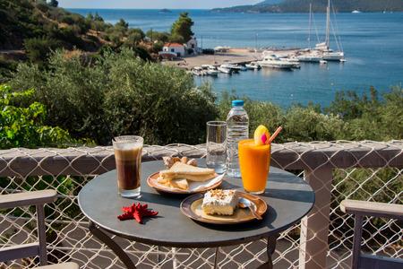 gastro: Coffee, orange juice, cheese ham toast, ekmek dessert, water for breakfast at greek tavern near the aegean sea with views of the marina and seascape. Magic breakfast during a sea vacation. Horizontal.