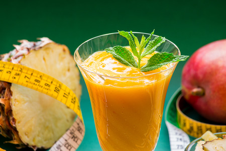 A glass of pineapple mango smoothie near ingredients, centimeter on a green background. Pineapple mango smoothie and centimeter. Horizontal. Daylight. Close.