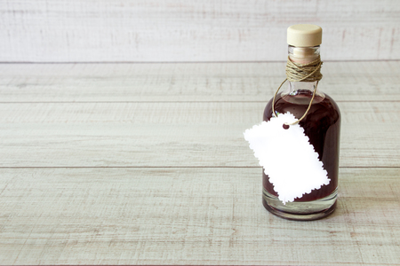 dressing treatment: Right a bottle with a dark liquid capped with white label beneath the inscription on a light wooden backgroundn left empty space. A glass bottle with a dark liquid. Horizontal. Daylight.