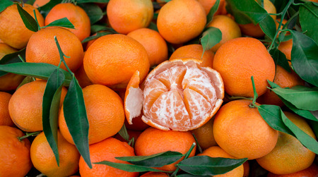 greek pot: One peeled tangerine on the background of tangerines. Tangerines for sale. Horizontal. Daylight.