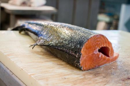 karkas: Zalm karkas ligt op een snijplank in de viswinkel voor het snijden filets. Zalm voor het snijden filets. Horizontaal. Daglicht. Stockfoto