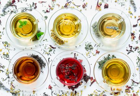 黒茶、緑、ハイビスカス、カモミール、ペパーミントの種類と六つのカップ、散乱お茶の白い背景でのラベンダーの葉します。6 タイプの散乱お茶の白地に茶の葉します。