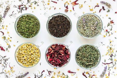 6 cups with different types of tea leaves black, green, hibiscus, chamomile, mint, lavender on white background of scattered tea leafs. Tea collection of six different types of tea leafs. Horizontal. Stock Photo
