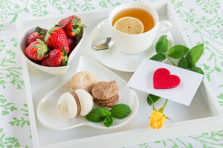 Breakfast in bed of green tea, strawberries, sweets and red heart, yellow rose, envelope on a white tray. Romantic breakfast in bed and love letter. Horizontal. DAylight. Close up.