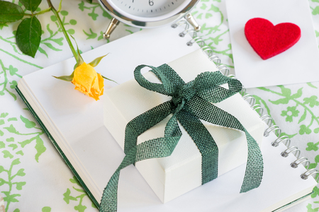 Gift box, yellow rose, envelope with heart, alarm clock. Romantic gift love confession concept. Horizontal. Daylight. Close