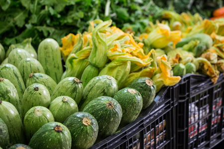 Fresh zucchini in a box on the counter in a grocery store for sale. Zucchini in a box for sale at the market. Horizontal. Selective focus. Close up. Stock Photo