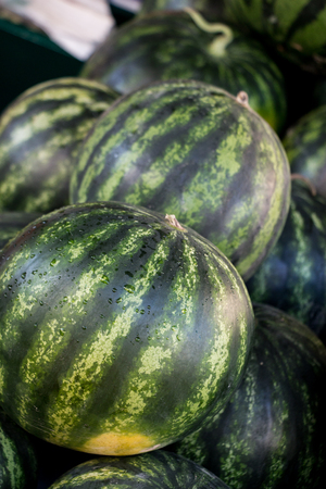Watermelon on a counter in a grocery shop. Watermelon background. Vertical.