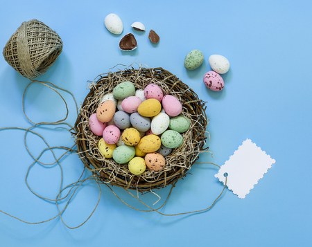 Multicolored quail eggs or small painted chocolate eggs in a basket nest isolated naer tag on a blue background. Horizontal. Top view. Close up.