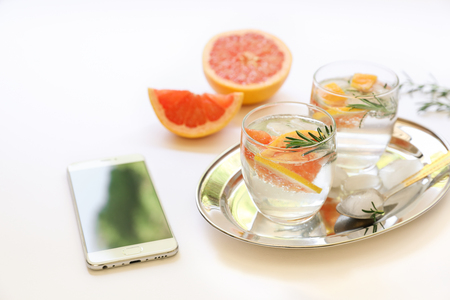 Detox drink with grapefruit, rosemary, ice and mobile near.