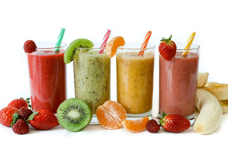 Four different smoothies of berry, banana with tangerine, kiwi, strawberries. Stock Photo