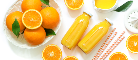Two glass bottles of fresh orange juice, straws and oranges isolated on white background. Top view. Close-up.