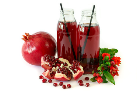 Two glass bottles of pomegranate juice, fruit, seeds and flowering branch of pomegranate tree isolated on white background. Horizontal. Close-up.