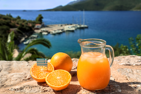 Fresh greek orange juice with ice, oranges on a stone surface by the seascape view, Kiparissi Laconia, Peloponnes, Greece. Horizontal. Daylight. Close-up.