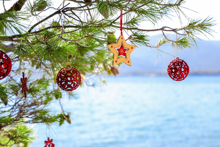 Christmas decorations hunging on branches of a pine tree growing on the beach of the Aegean sea, New Year holidays by the sea concept. Horizontal. Outdoor.