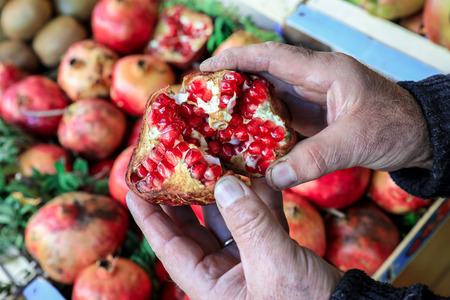 seller: Half of the ripe pomegranate fruit in the hands of the seller in the greek vegetable shop on the background of pomegranate fruits. Horizontal. Outdoor. Close-up.