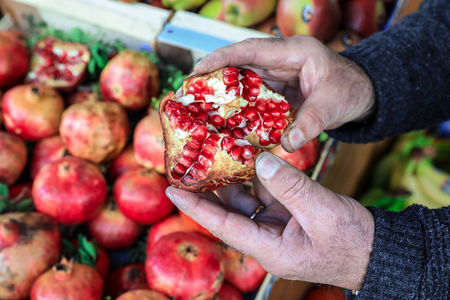 seller: Half of the ripe pomegranate fruit on the palms of the seller in the greek vegetable shop.