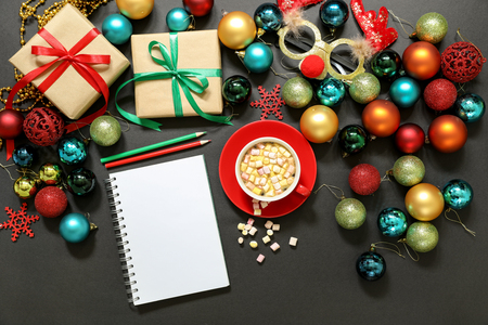 Christmas tree toys different colors balls, gifts, deer mask, notebook, pencils, cup of coffee with marshmallows on a dark background