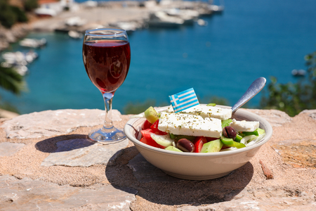 A glass of red wine and bowl of greek salad with greek flag on by the sea view, summer greek holidays concept. Stock Photo