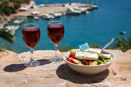 Two glasses of red wine and bowl of greek salad with greek flag on by the sea view, summer greek holidays concept. Foto de archivo