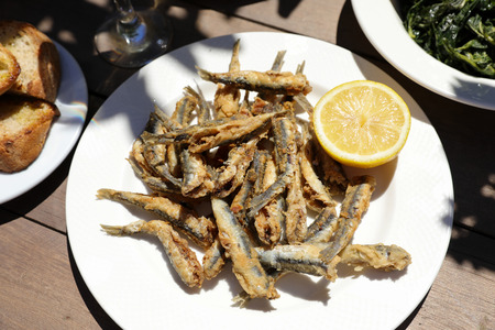 Fried fresh anchovies or gavros tiganitos served with half of lemon on white plate next to bread plate, greens salad dish in the greek tavern. Horizontal. Close-up. Daylight. View from above.