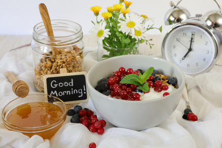 A bowl with yogurt, granola, blueberries and cranberries, granola jar, honey and flowers, alarm clock, good morning and healthy breakfast concept.