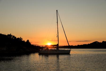 Beautiful sunset sailboat anchoring in a bay near Porto Heli, Peloponnese, Greece. Horizontal. Reklamní fotografie
