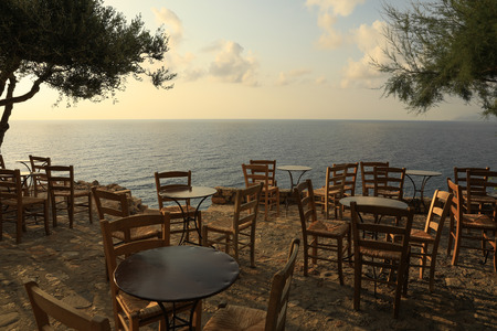 Iron tables and wooden chairs, typical traditional Greek cafes, overlooking the roofs of houses and the sea in Monemvasia, Peloponnese, Greece.