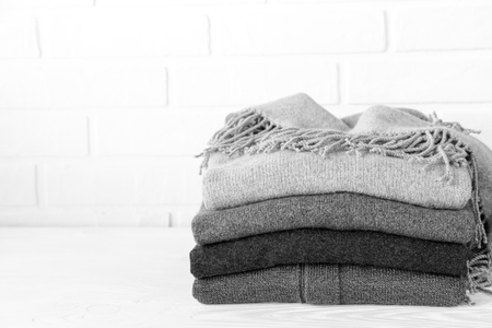 Stack of cozy knitted sweaters in gray preparing for winter cold concept black and white photo. Foto de archivo