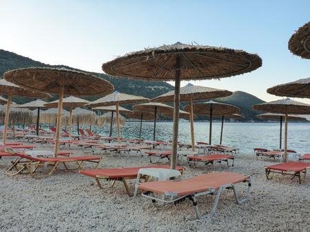 Summer evening straw umbrellas and sunbeds on a beautiful Antisamos beach of Kefalonia island, Ionian sea, Greece. Stock fotó