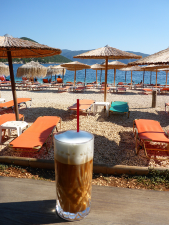 Summer morning with freddo cappuccino greek cold coffee drink on the backgraund straw umbrellas and sunbeds of Antisamos beach, Kefalonia island, Ionian sea, Greece.