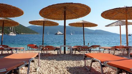 Summer morning straw umbrellas and sunbeds on a beautiful Antisamos beach of Kefalonia island, Ionian sea, Greece. Horizontal.