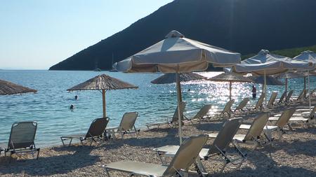 Summer umbrellas and sunbeds on a beautiful Antisamos beach of Kefalonia island, Ionian sea, Greece. Horizontal. Stock fotó