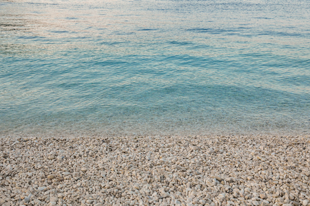 Summer evening crystal clear water and pebbles on a beautiful Antisamos beach of Kefalonia island, Ionian sea, Greece. Horizontal. Close-up.