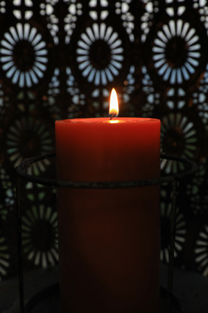 A red candle burns in the evening. Vertical. Standard-Bild