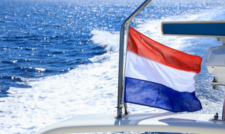 Waving flag of Holland on the stern of a yacht traveling in the waters of the Aegean sea in Greece.