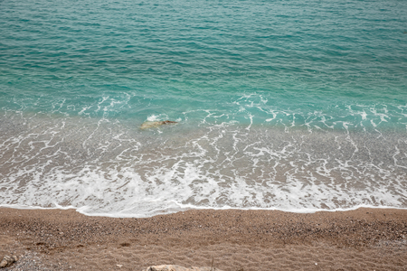 Fantastic turquoise crystal clear water, sand and pebbles of the Agia Kyriaki beach in the Kiparissi Lakonia village, Peloponnese, Zorakas Bay, Greece, evening - May 2019.