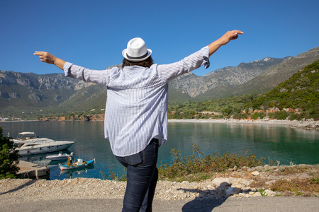 Happy traveller woman enjoys her spring vacation time in the Kiparissi Lakonia village, Peloponnese, Zorakas Bay, Greece, May 2019.
