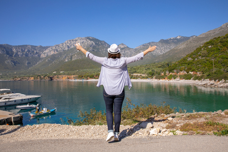 Stylishly dressed girl in blue jeans, white hat, shirt and sneakers enjoys traveling during her spring vacation in the Kiparissi Lakonia village, Peloponnese, Zorakas Bay, Greece, May 2019.