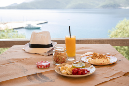 Healthy breakfast from yogurt, sliced banana, kiwi, strawberries, granola and glass of fresh orange juice in a beautiful location with sea views