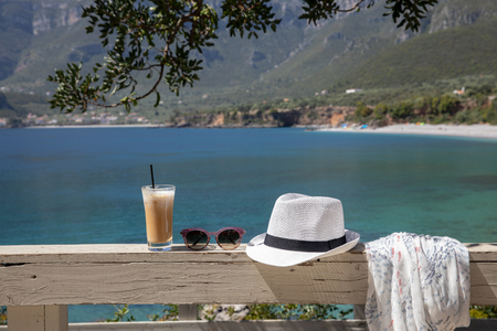 Summer concept  of frappe iced coffee glass, sunglasses, white hat, light scarf in a beautiful location with sea views Stok Fotoğraf