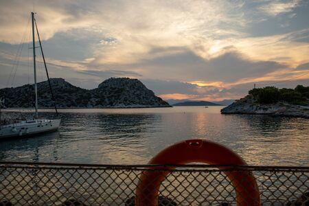 Summertime beautiful sunset as seen from the beach of Aponissos, Agistri island, Saronic gulf, Greece. Horizontal.