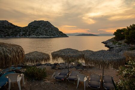 Summertime evening straw umbrellas and sun beds beautiful view from the beach of Aponissos, Agistri island, Saronic gulf, Greece.