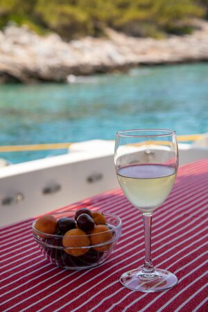 A glass of cold white wine and a bowl of cherries and apricots on the yacht table off the coast of Agistri island, Saronic Gulf, Greece.