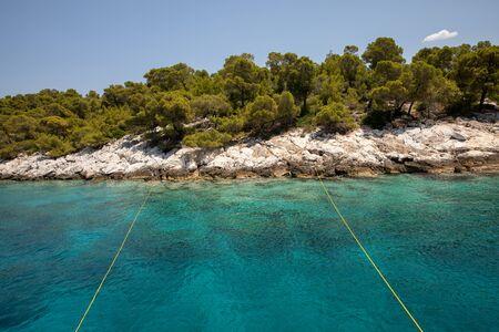 Summertime turquoise crystal clear water near the Aponissos beach, Agistri island, Saronic gulf, Greece.