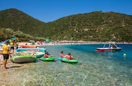 August 12th, 2019. Children getting ready to ride on water tube during summer vacation. Water sports and fun in summer at the Antisamos beach, Sami Kefalonia, Greece. Horizontal.