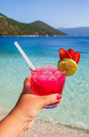 Woman holding fresh and tasty strawberry-daiquiri cocktail on the Antisamos beach, Sami Kefalonia island, Greece.